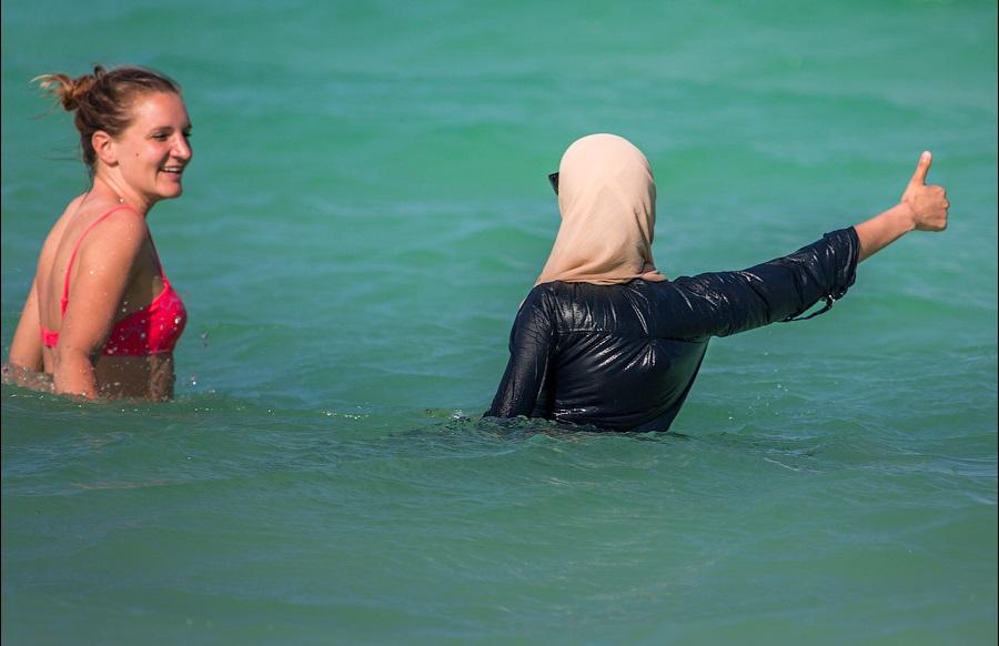 Туристка в бикини и молодая мусульманка в купальнике буркини