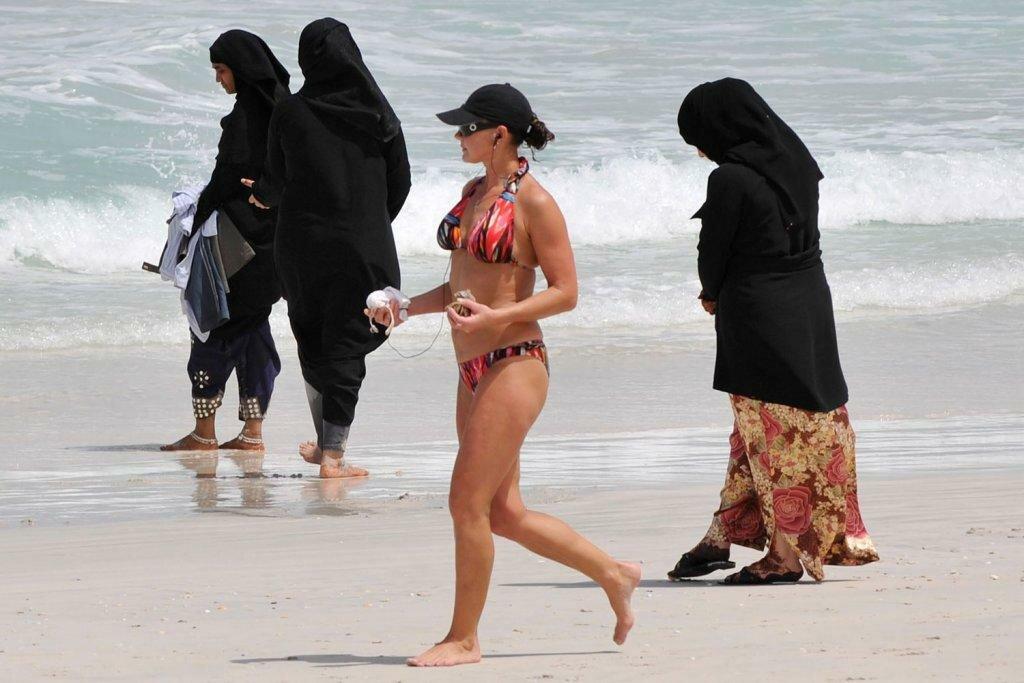 На пляже в ОАЭ: мусульманки в буркини, туристка в бикини